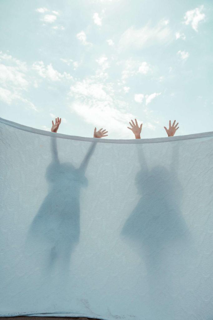 Children Hiding Behind Sheet